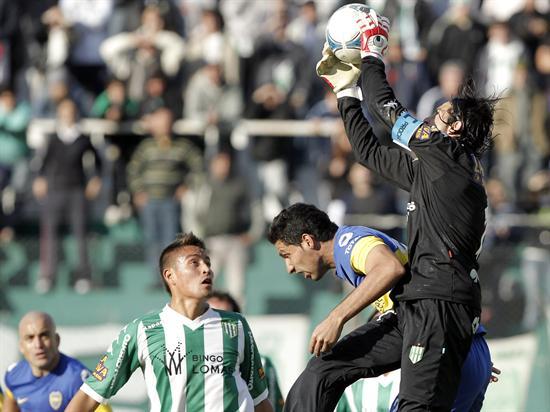 Juan Insaurralde (i) de Boca Juniors disputa el balón con el arquero Cristian Lucchetti (d) de Banfield. Foto: EFE