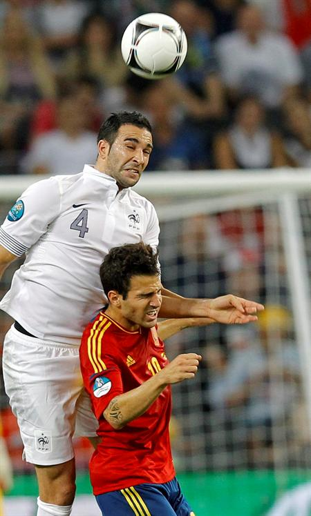 El jugador de la selección española, Cesc Fábregas (dcha), lucha por un balón con el internacional francés, Adil Rami. Foto: EFE