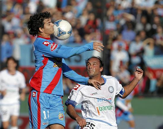 El jugador de Arsenal Emilio Zelaya (i) cabecea el balón ante la marca de Gastón Turus (d), de Belgrano. EFE