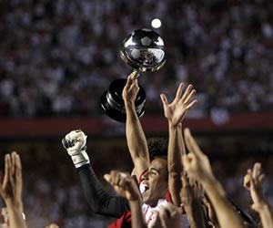 El delantero del club brasileño de Sao Paulo, Lucas, sostiene el trofeo de Campeón de la Copa