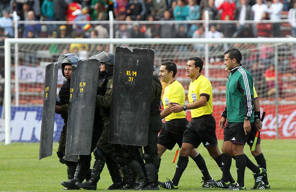 El árbitro chileno Enrique Osses (c) sale escoltado por la policía boliviana al finalizar el encuentro. Foto: EFE