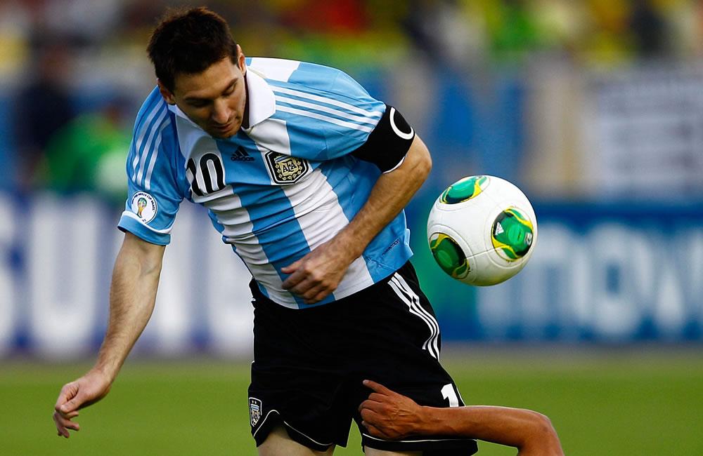 El jugador de Ecuador Fernado Saritama (abajo) disputa un balón con Lionel Messi (arriba) de Argentina. EFE