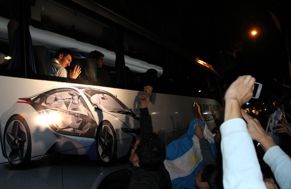 Aficionados toman fotografías al paso del autobús con la selección argentina. EFE