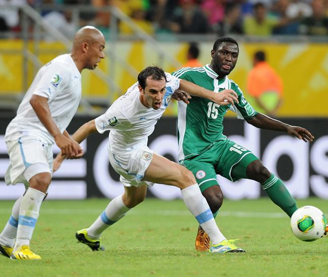 El jugador Diego Godin (c) de Uruguay disputa un balón con Michael Babatunde (d) de Nigeria. Foto: EFE