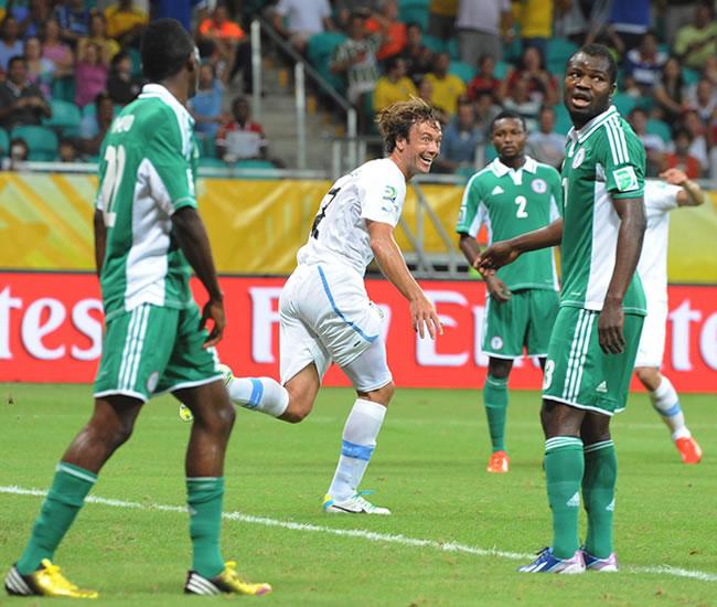 El jugador de Uruguay Christian Rodríguez (i) disputa un balón con Uwa Echiejile (d) de Nigeria. Foto: EFE