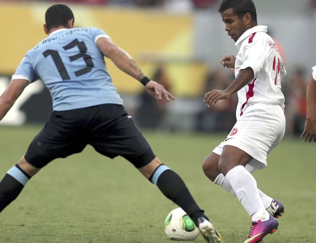 El delantero de la selección de Tahití, Samuel Hnanyine (d), controla el balón junto a Aguirregaray, defensa de Uruguay, durante el partido, correspondiente al Grupo B de la Copa Condeferaciones. Foto: EFE