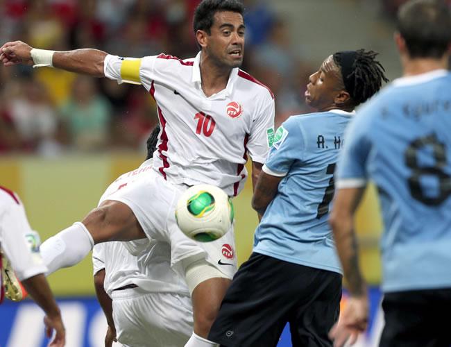 El delantero de Uruguay Abel Hernández (2d) pelea un balón con el defensa de Tahiti Nicolás Vallar, durante el correspondiente al Grupo B de la Copa Confederaciones. Foto: EFE