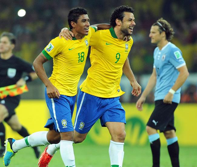 Los jugadores de la selección de fútbol de Brasil Paulinho (i) y Fred (c) celebran ante Uruguay. Foto: EFE