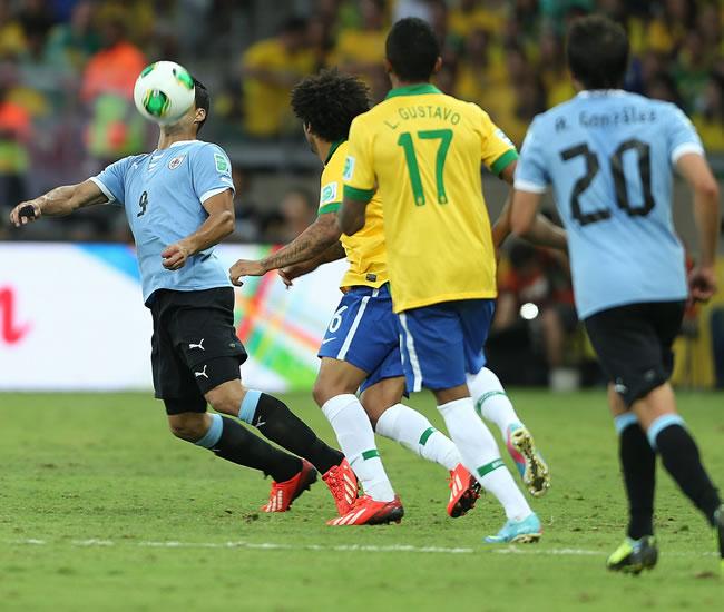 El delantero de la selección de Uruguay, Luis Suárez (i), controla el balón junto a Marcelo Vieira (2i) y Luiz Gustavo (3i), de Brasil. Foto: EFE