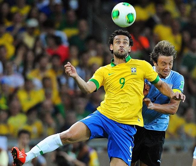 El jugador de Brasil Fred (i) disputa el balón con el uruguayo Diego Lugano. Foto: EFE