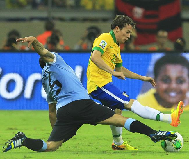 El jugador de Uruguay Walter Gargano (i) disputa el balón con el brasileño Bernard. Foto: EFE