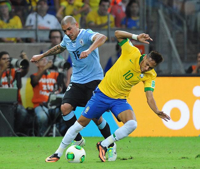 El jugador de Uruguay Maximiliano Pereira (i) disputa el balón con el brasileño Neymar. Foto: EFE