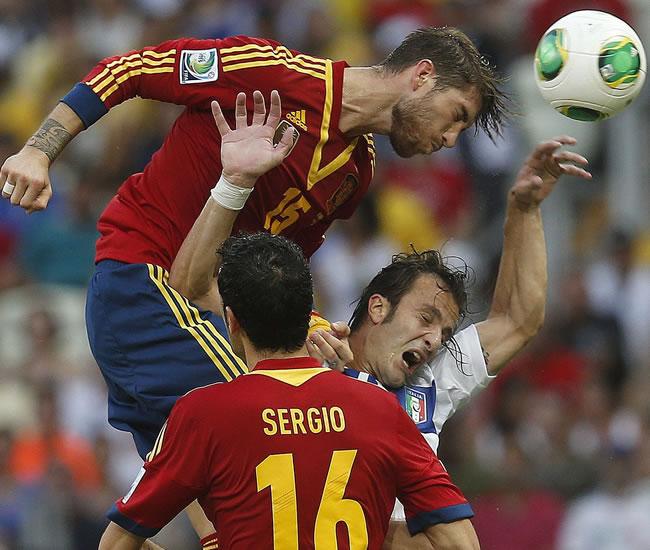 El defensa español Sergio Ramos (arriba) cabecea el balón ante su compañero, Sergio Busquets (c) y el delantero de Italia. Foto: EFE
