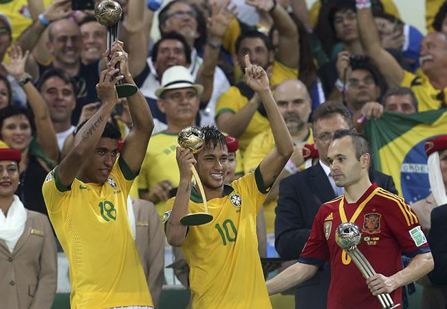 Los jugadores de la selección brasileña Paulinho (i) y Neymar muestran sus trofeos en presencia de Iniesta (d), de España. Foto: EFE