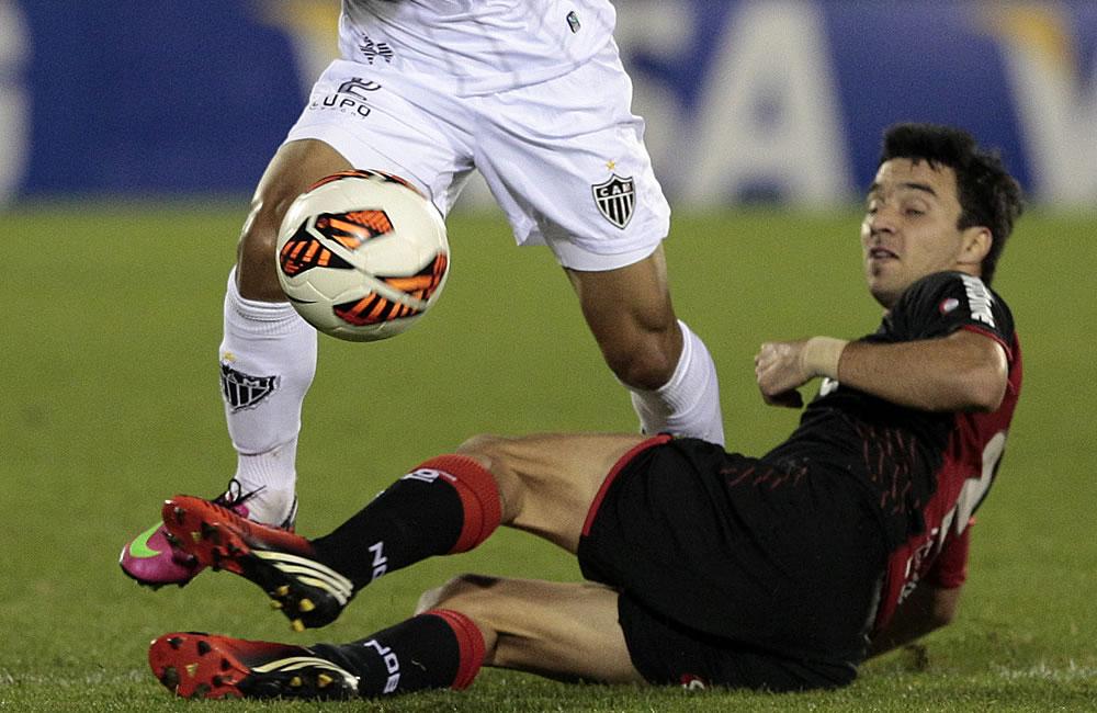 El jugador de Newell's Old Boys Ignacio Scocco (d) disputa el balón con Gilberto Silva (i) del Atlético Mineiro. Foto: EFE