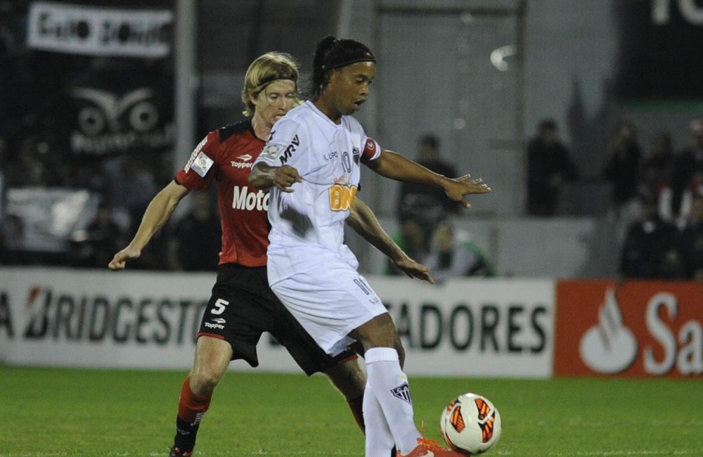 El jugador de Newell's Old Boys Diego Mateo (i) disputa el balón con el jugador Ronaldinho del Atlético Mineiro. Foto: EFE