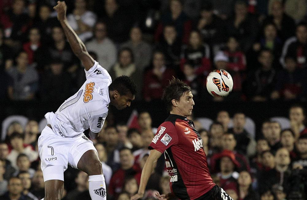 El jugador de Newell's Old Boys (d) Santiago Vergini disputa el balón con el jugador Jo del Atlético Mineiro. Foto: EFE