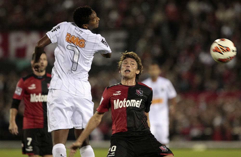 El jugador de Newell's Old Boys (d) Javier Heinze disputa el balón con el jugador Jo del Atlético Mineiro. Foto: EFE