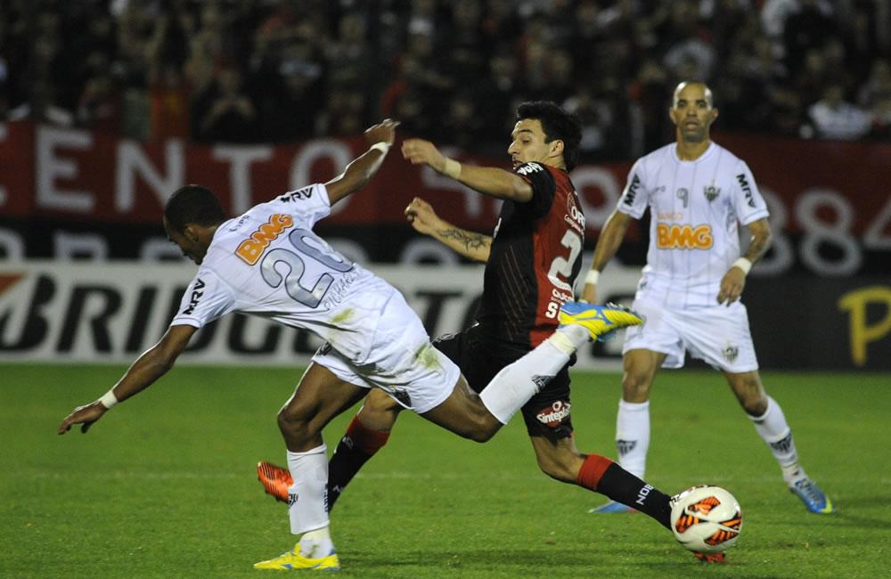 El jugador de Newell's Old Boys (c) Ignacio Scocco de Newells disputa el balón con el jugador Richarlyson del Atlético Mineiro. Foto: EFE