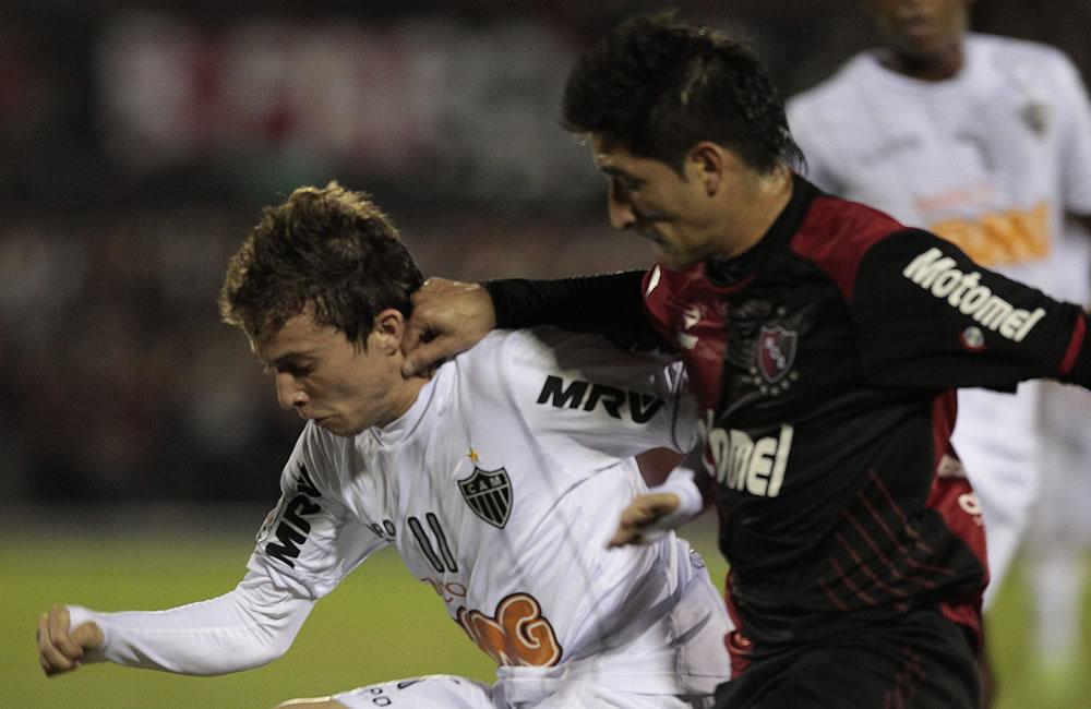 El jugador de Newell's Old Boys (d) Milton Casco disputa el balón con el jugador Bernard del Atlético Mineiro. Foto: EFE