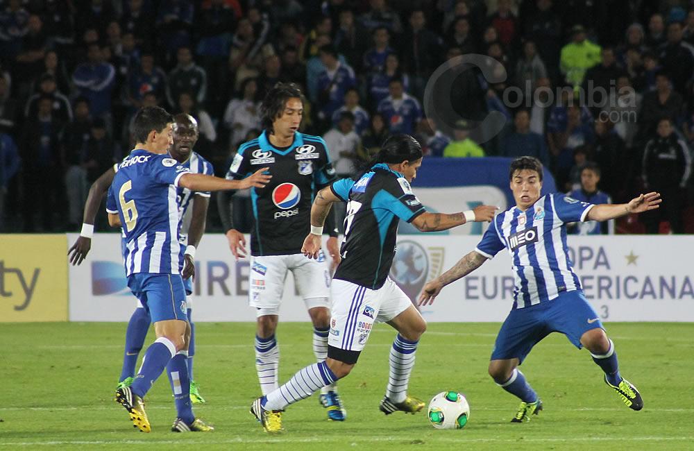 Dayro Moreno de Millonarios (c) trata de avanzar con el balón ante la marca de los jugadores de Oporto. Foto: Interlatin