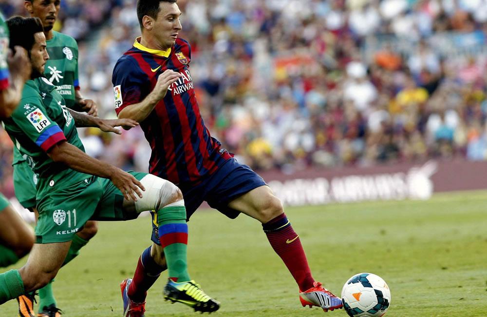 El delantero argentino del Barcelona, Leo Messi (d), pelea un balón con el centrocampista del Levante Rubén García. Foto: EFE