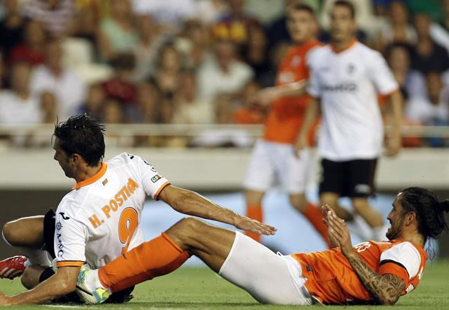 El delantero portugués del Valencia Hélder Postiga (i) disputa el balón con el defensa argentino Marcos Angeleri, del Málaga. Foto: EFE
