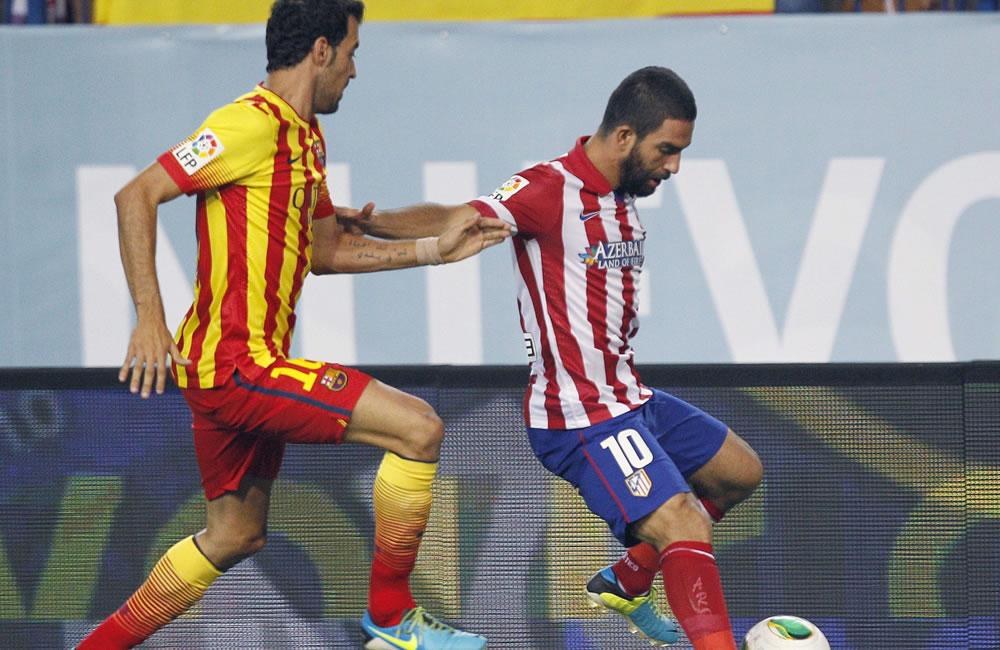 El jugador turco del Atlético de Madrid Arda Turan (d) es perseguido por Sergi Busquets, del FC Barcelona. Foto: EFE