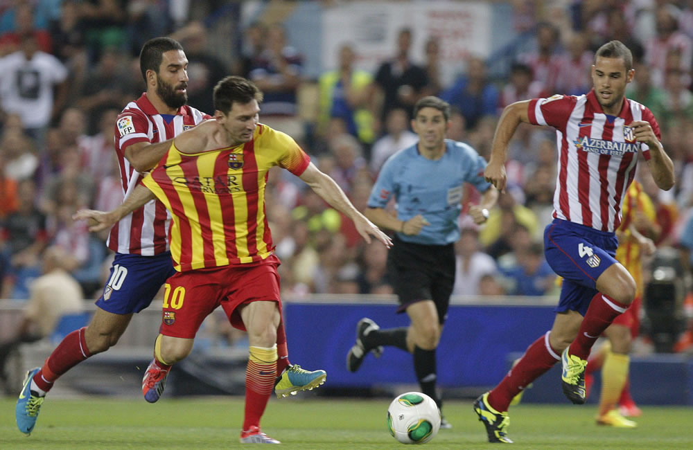 El centrocampista turco del Atlético de Madrid Arda Turan (i) agarra al argentino Leo Messi (c), del FC Barcelona. Foto: EFE