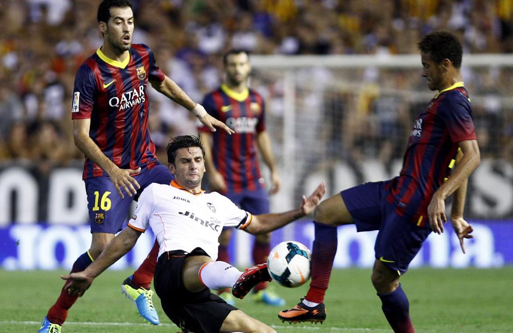 El delantero portugués del Valencia Helder Postiga (c) pelea un balón con el delantero brasileño Neymar da Silva (d). Foto: EFE