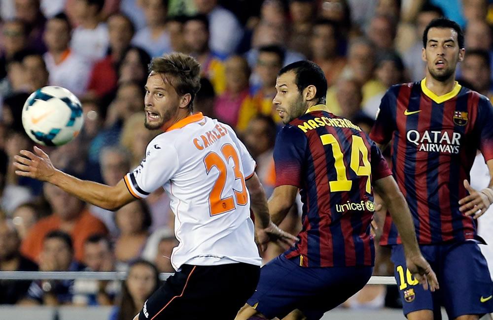 El defensa argentino del FC Barcelona Javier Mascherano (c) lucha el balón con Sergio Canales (i), del Valencia CF. Foto: EFE