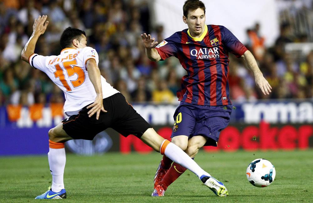 El delantero argentino del FC Barcelona Leo Messi (d) lucha el balón con Javi Fuego, del Valencia CF. Foto: EFE