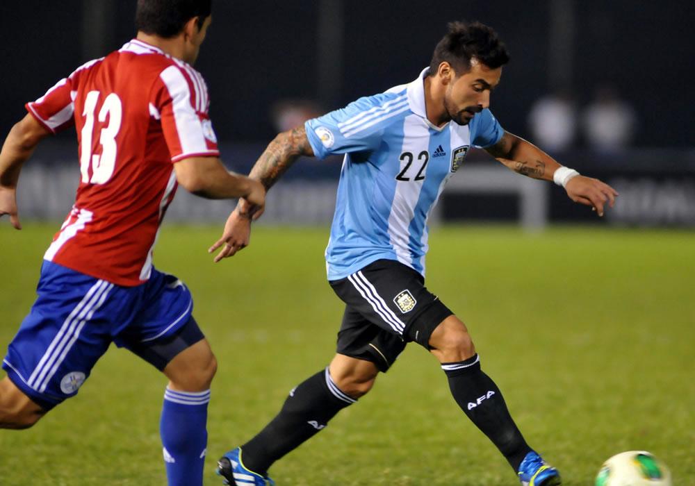 Miguel Samudio (i) de Paraguay disputa el balón con Ezequiel Lavessi (d) de Argentina. Foto: EFE