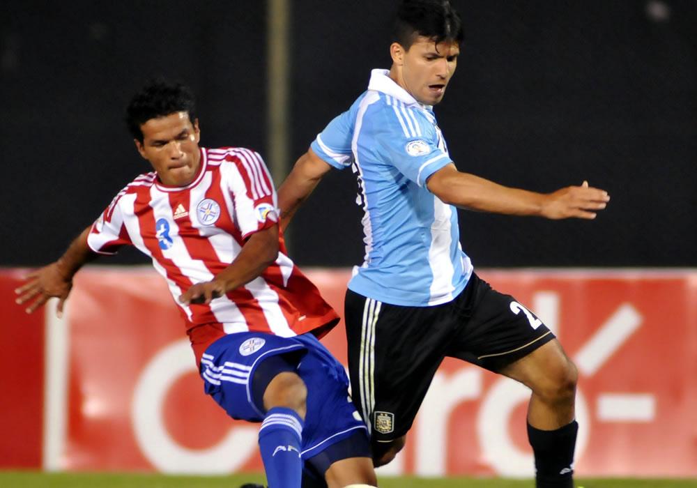 Salustiano Candia (i) de Paraguay disputa el balón con Sergio Agüero (d) de Argentina. Foto: EFE
