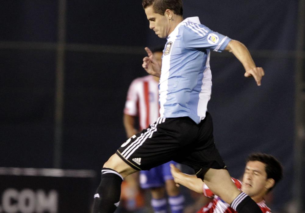 Cristian Riveros (abajo) de Paraguay disputa el balón con Fernando Gago (arriba) de Argentina. Foto: EFE