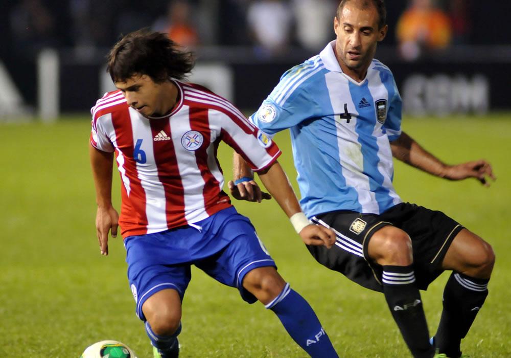 Óscar Romero (i) de Paraguay disputa el balón con Pablo Sabaleta (d) de Argentina. Foto: EFE