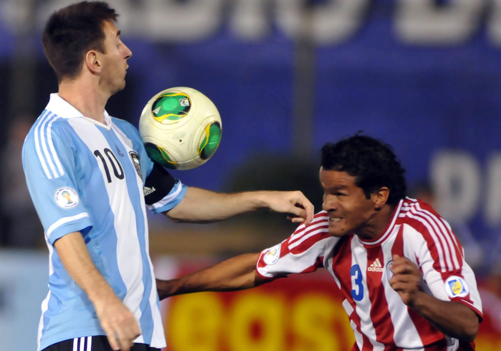 Salustiano Candia (d) de Paraguay disputa el balón con Lionel Messi (i) de Argentina. Foto: EFE