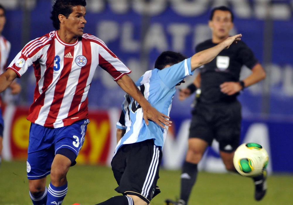 alustiano Candia (d) de Paraguay disputa el balón con Lionel Messi (i) de Argentina. Foto: EFE