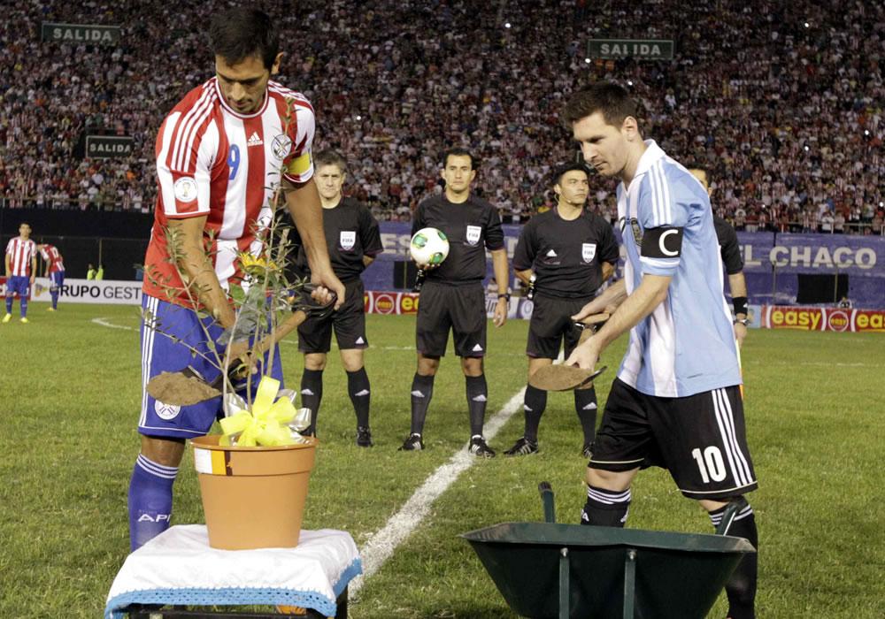 Roque Santa Cruz (i) de Paraguay y Lionel Messi (d) de Argentina ponen arena en una planta de olivo. Foto: EFE