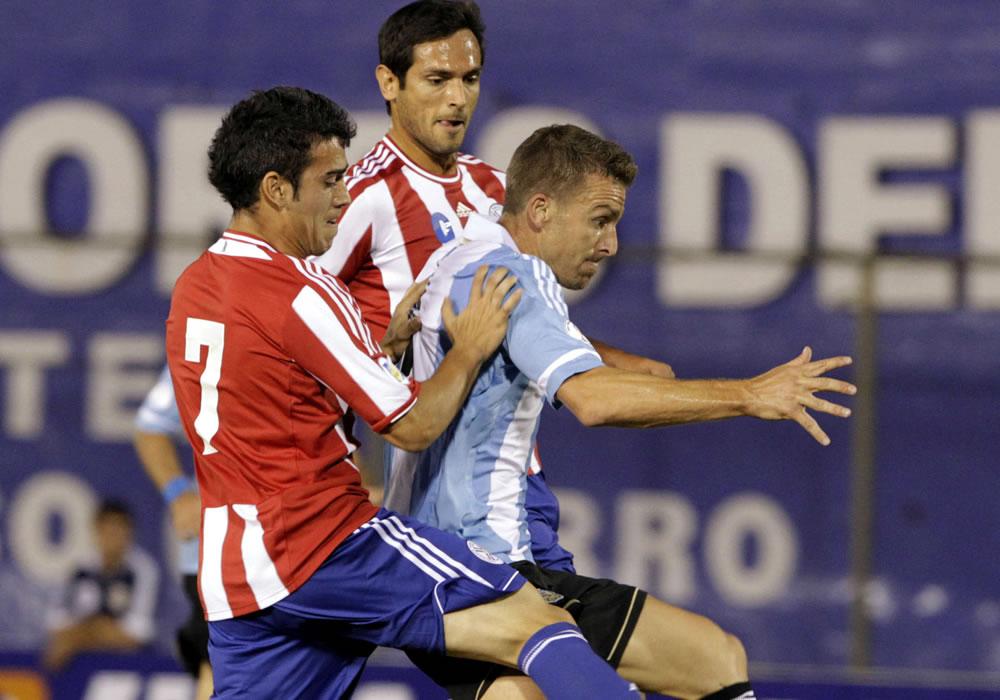 Roque Santa Cruz (c) y Ángel Di María (i) de Paraguay disputan el balón con Lucas Biglia (d) de Argentina. Foto: EFE