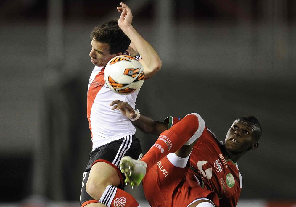 El jugador de River Plate de Argentina Federico Andrada (i) ante Robert Arboleda (d) de la Liga de Loja. Foto: EFE