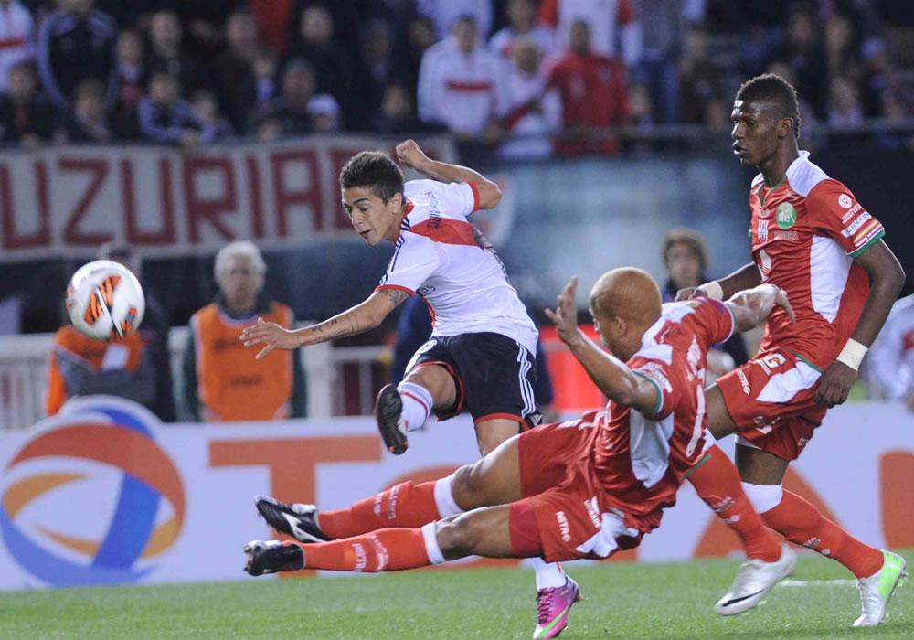El jugador de River Plate de Argentina Manuel Lanzini (i) patea ante Jimmy Bermúdez (c) de la Liga de Loja. Foto: EFE