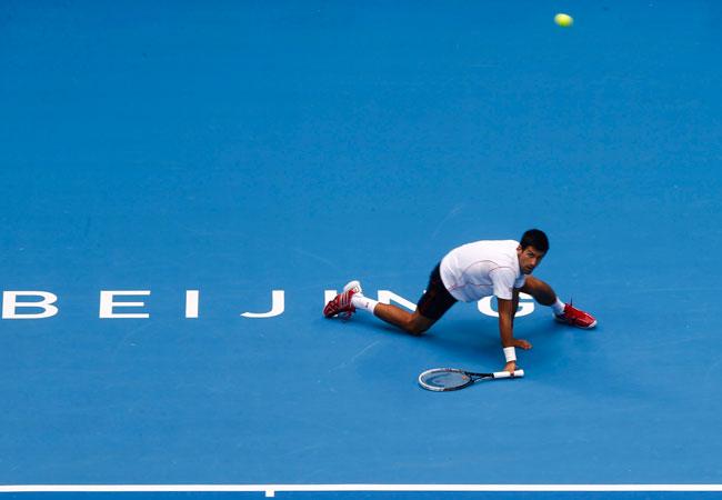 El tenista serbio Novak Djokovic devuelve una bola al checo Lukas Rosol durante el partido que enfrentó a ambos en el torneo WTA de Pekín. Foto: EFE