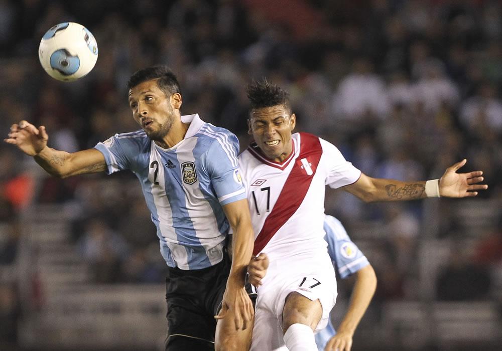 El jugador de Argentina Ezequiel Garay (i) disputa un balón con Edwin Gómez de Perú. EFE