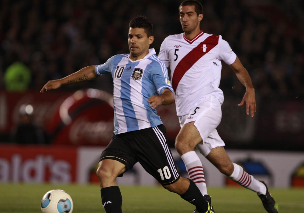 El jugador de Argentina Sergio Agüero (i) disputa un balón con Gianmarco Gambetta de Perú. Foto: EFE