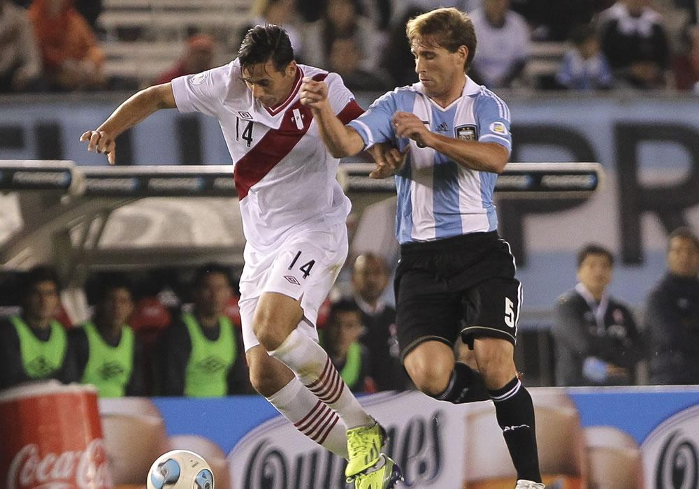El jugador de Argentina Lucas Biglia (d) disputa un balón con Claudio Pizarro de Perú. Foto: EFE
