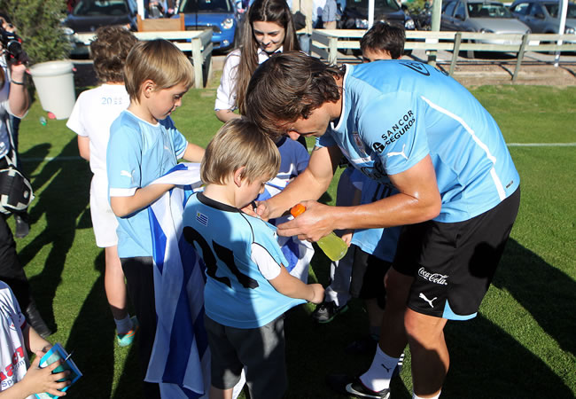 El jugador de la selección de Uruguay Diego Lugano (d), firma autógrafos luego de un entrenamiento. Foto: EFE
