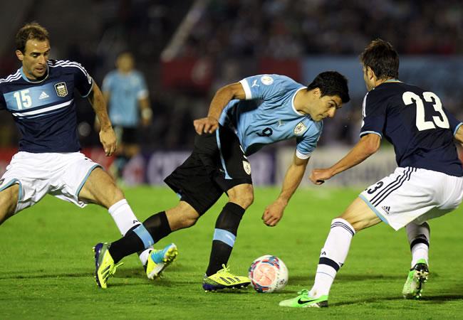 El jugador de la selección argentina José Basanta (d) disputa el balón con Luis Suárez (c) de Uruguay. Foto: EFE