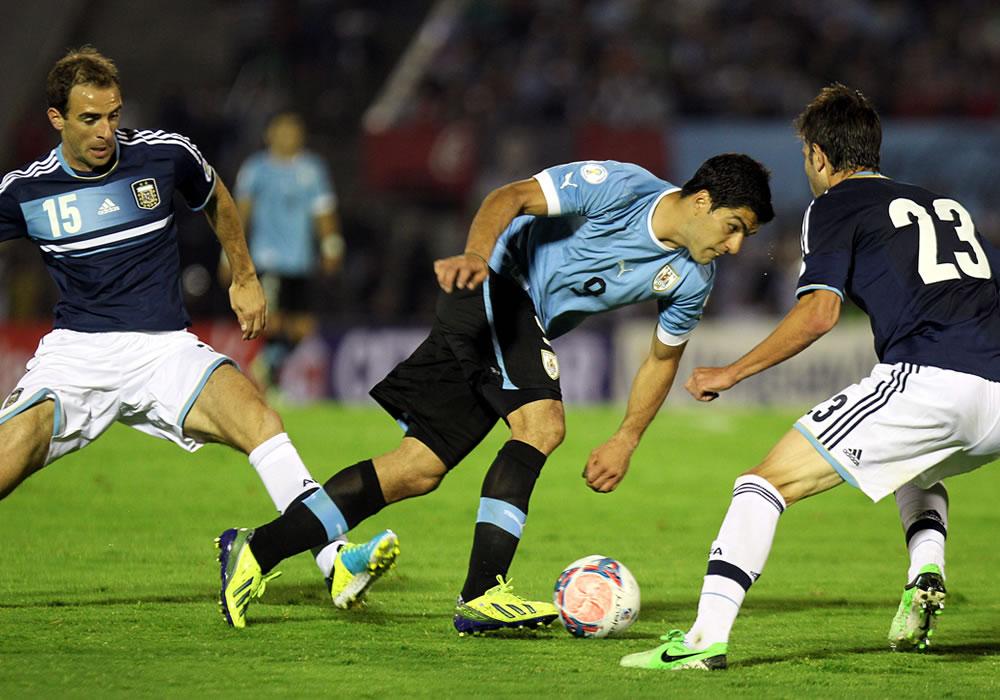 El jugador de la selección argentina José Basanta (d) disputa el balón con Luis Suárez (c) de Uruguay. EFE