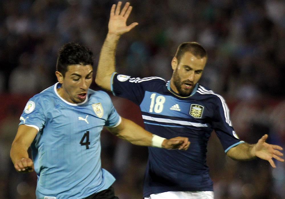 El jugador de la selección argentina Rodrigo Palacio (d) disputa el balón con Jorge Fucile (i) de Uruguay. EFE